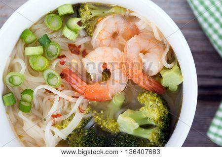 asian prawn rice noodle soup closeup on rustic table