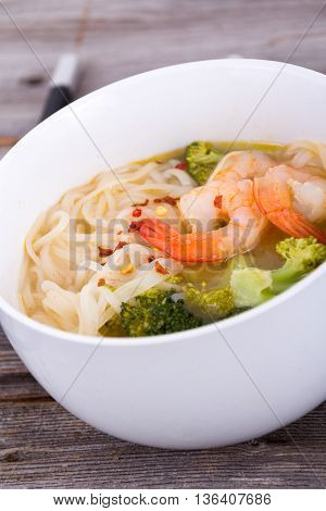 asian prawn rice noodle soup closeup on rustic table