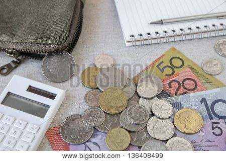 Australian money AUD with calculator notebook and small money pouchselective focus on 1 dollar coin