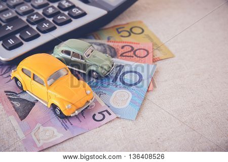 Toy cars with AUD Australian money and calculator copy space toning background for car insurance car LoanCar business concept