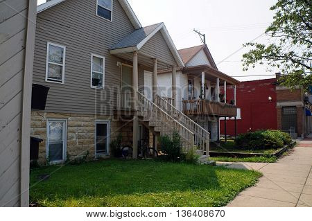 JOLIET, ILLINOIS / UNITED STATES - JUNE 30, 2015: The tall front steps and porch of a small home in downtown Joliet, Illinois.