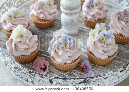 Purple cupcakes with sugared edible flowers on vintage cake stand