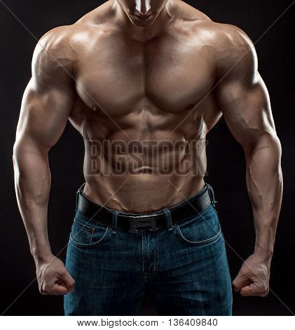 Muscular bodybuilder guy doing posing over black background. Naked torso in jeans. Close-up