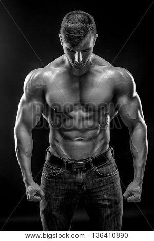 Muscular bodybuilder guy doing posing over black background. Naked torso in jeans. Black and white, b w