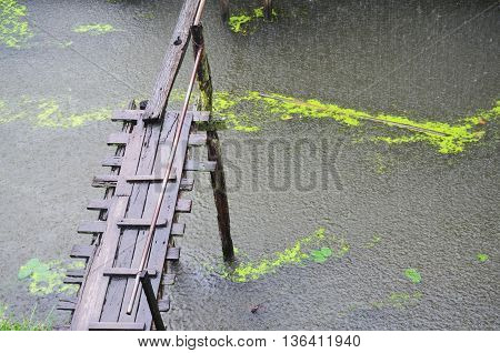 wood bridge and raining in canal in thailand