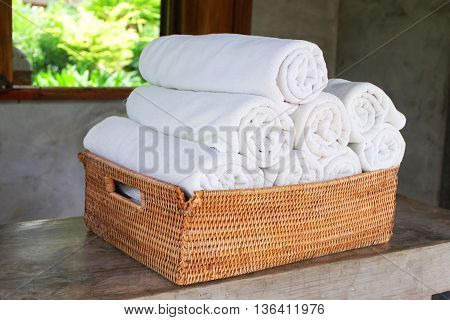 white towel roll in the basket on the table