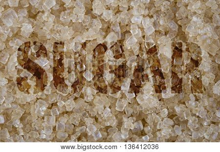 Sugar word screened on background of close focus brown cane sugar