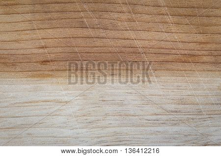 Background of used cutting board in two tones color which made from wood having scratches from knife
