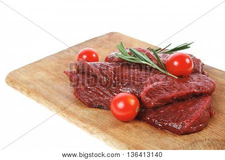 fresh raw beef steak with cherry tomatoes rosemary twig on wood cut board isolated on white background