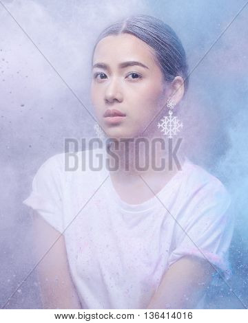 High fashion model girl portrait with colorful powder. Beauty woman with bright color makeup.