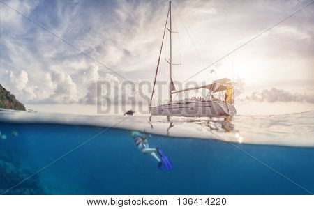 Split shot with young man in swim suit underwater and sail boat on the surface