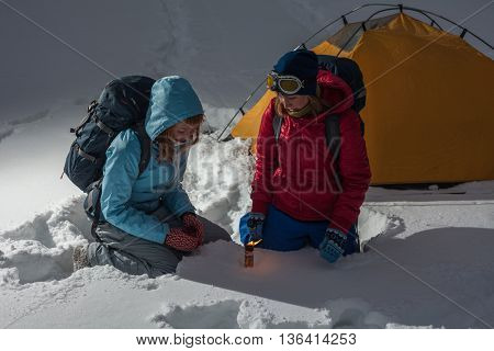 Two backpackers burn rescue signal fire in a winter field with tent on the background