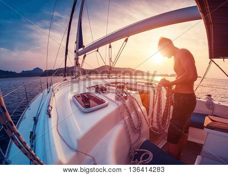 Young man working with rope on the sailing boat