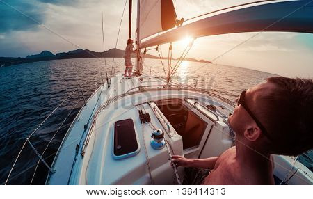 Young lady and man working with sail and ropes on the sailing boat