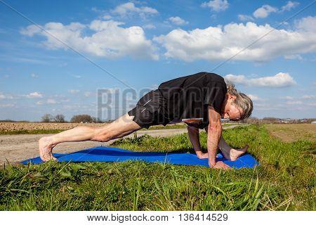 on an sunny day this man enjoys visvamitrasana yoga in nature