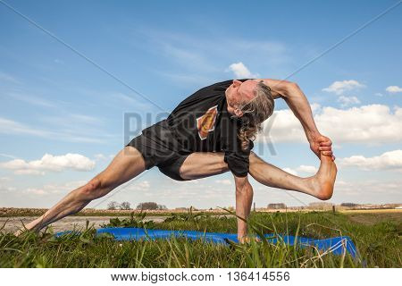 on an sunny day this man enjoys Ayurveda and yoga in nature