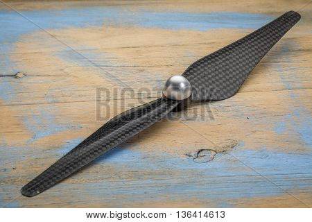 carbon fiber drone propeller against grunge wood