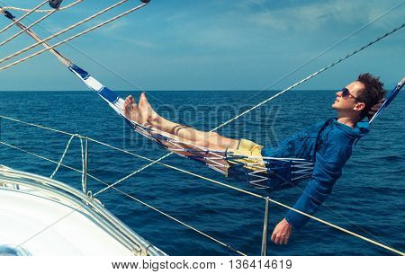 Man relaxing in the hammock set on the sail boat while sailing in the open sea