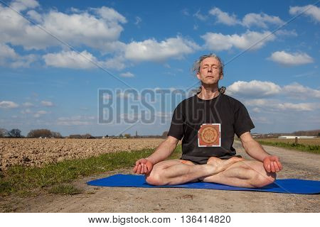 on an sunny day this man enjoys Lotus Pose yoga in nature