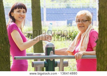 Senior And Young Woman With Mineral Water On Outdoor Gym, Healthy Lifestyle