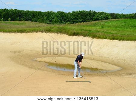 Golfer Hitting Ball with Club. Golfer on golf course.