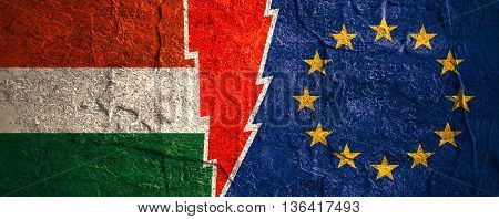 Image relative to politic relationships between European Union and Hungary. National flags divided by high voltage sign. Concrete textured