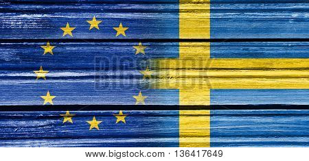 Image relative to politic relationships between European Union and Sweden. National flags textured by wood