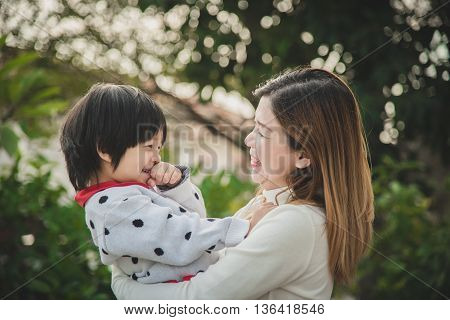 Happy asian mother playing with her son in the park