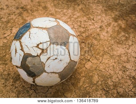 Old soccer ball on Dry and cracked ground texture