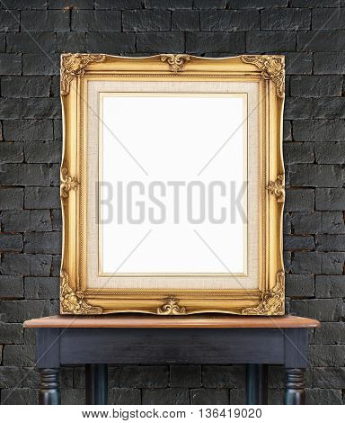 Blank Vintage Golden Photo Frame Lean At Black Brick Wall On Wood Table