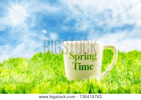 White Coffee Cup With Spring Time Word On Green Grass With Blue Sky And Sunburst