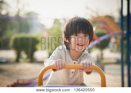 Cute asian child riding seesaw board at the playground under sunlight