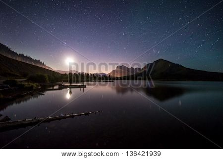 Moon rises over lake in the rockies near banff, alberta, canada
