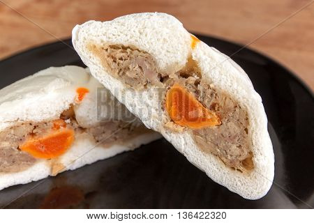 Bread split half show pork and salted egg on Black dish a wood plate background. Close up