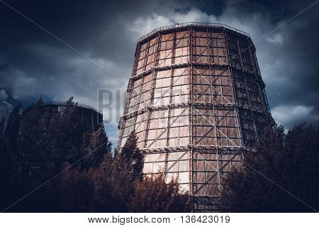 brightly lighted tube thermal power plant dark in cloudy weather, filter