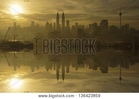 Silhouette of Kuala Lumpur City during dramatic sunrise on hazy day.