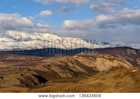 Scenic view with the beautiful mountains with snow and glaciers and the valley in the sunlight against the blue sky and clouds at dawn
