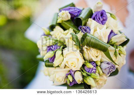 Violet Wedding Bouquet On Hand Of Bride