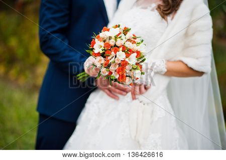 Wedding bouquet at hands of newlyweds at wedding