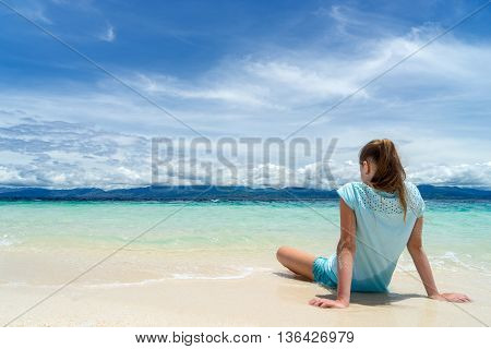 young beautifull girl is sitting on the white sand of tropical beach near turquoise sea under cloudy sky at sunny day