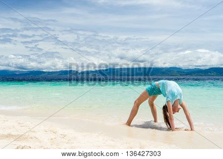 young slim teen girl do gymnastic exercise at white sand beach of tropical sea under blue sky at sunny day