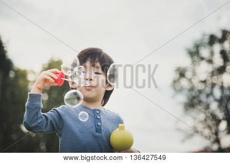 Cute asian child is blowing a soap bubblesvintage filter