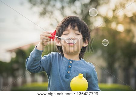 Cute asian child is blowing a soap bubbles