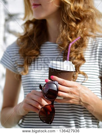 Sunglasses And Disposable Coffee Cup In The Woman Hands