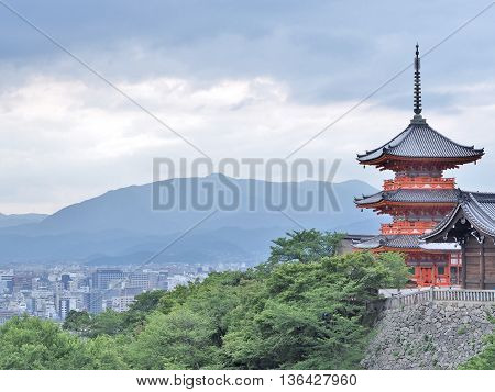 Red Pagoda with city view at Kiyomizu or Kiyomizu-dera temple in Kyoto, Japan. The temple is part of the Historic Monuments of Ancient Kyoto UNESCO World Heritage site.