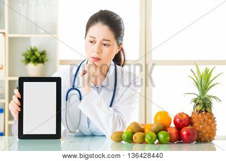 Doctor Nutritionist With Fruits And Holding Digital Tablet Fell Doubt