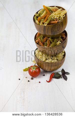 Raw pasta in wooden bowls and spices