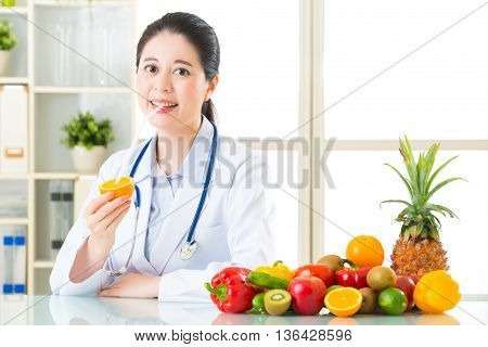 Young Asian Nutritionist Drinking Orange Juice And Smiling