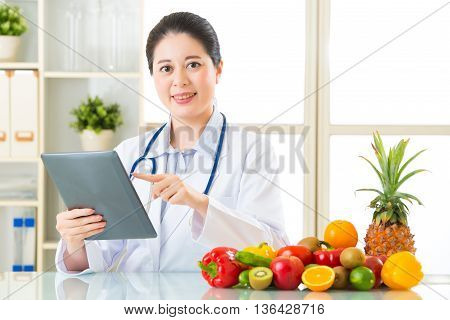 Doctor Nutritionist Using Digital Tablet With Fruits And Vegetable