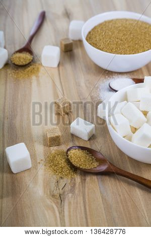 Cane and white sugar in a white bowls on the table